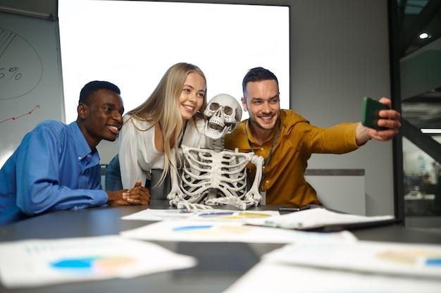 Gestionnaires drôles, selfie avec squelette au bureau informatique