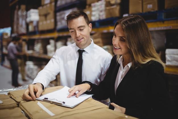 Gestionnaires d'entrepôt examinant le presse-papiers sur des boîtes