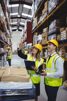 Gestionnaires d'entrepôt examinant le presse-papiers avec casques