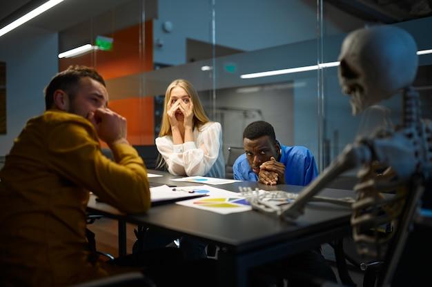 Gestionnaires et squelette effrayés dans le bureau informatique, plaisanterie
