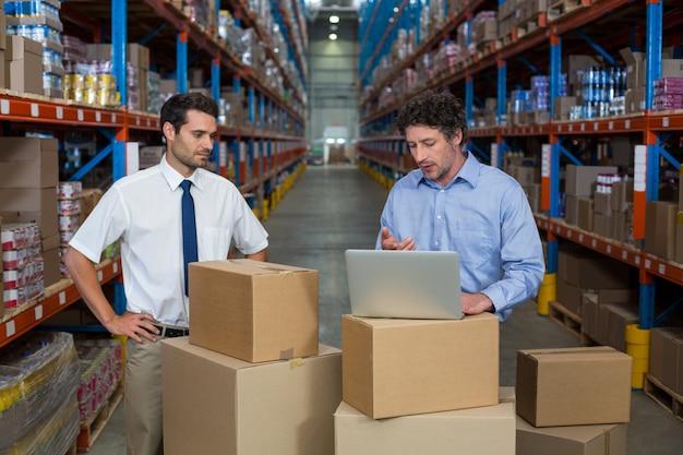 Les gestionnaires travaillant avec un ordinateur portable mis sur une boîte en carton