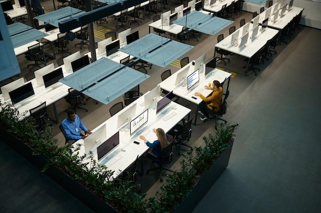 Les gestionnaires travaillent sur des ordinateurs dans le bureau informatique, vue de dessus
