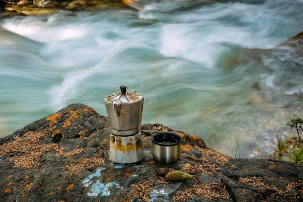 Geyser de café et une tasse en fer sur une grande pierre moussue