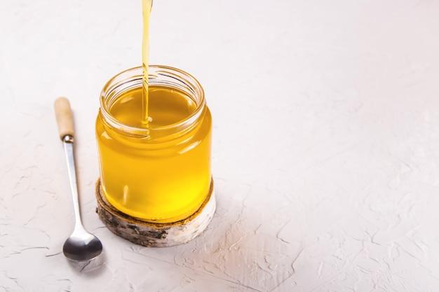 Ghee liquide fait maison ou beurre clarifié en pot transparent.