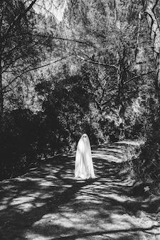 Ghost debout sur une passerelle dans un parc sombre