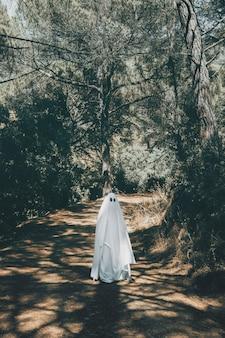 Ghost marchant sur une passerelle dans un parc sombre