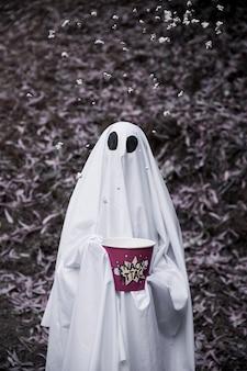 Ghost tenant une boîte de pop-corn avec du pop-corn dans l'air