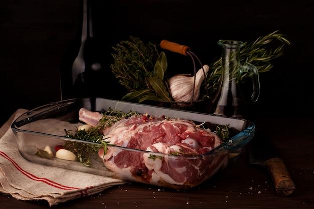 Gigot d'agneau cru prêt à rôtir avec ail et fines herbes