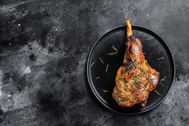 Gigot d'agneau cuit au four. fond sombre. vue de dessus. copiez l'espace.