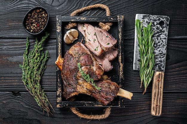 Gigot d'agneau de mouton rôti tranché dans un plateau en bois avec couperet à viande. table en bois noir. vue de dessus.