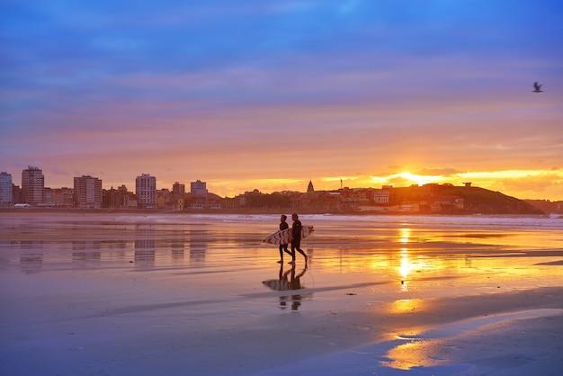 Gijon au coucher du soleil sur les surfeurs de la plage san lorenzo dans les asturies