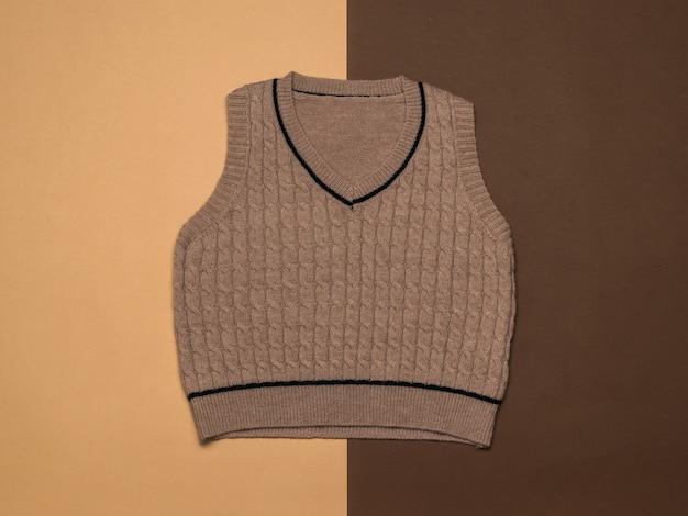 Gilet femme tricoté sur fond de deux couleurs marron. vêtements tricotés classiques à la mode.