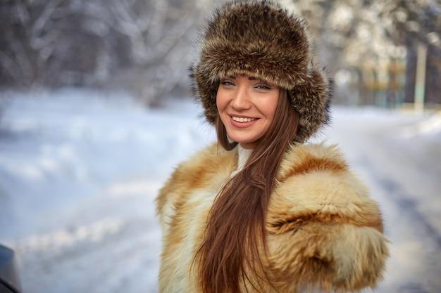 Gilet de fourrure et chapeau d'hiver sur la belle jeune femme de race blanche en hiver forêt ensoleillée