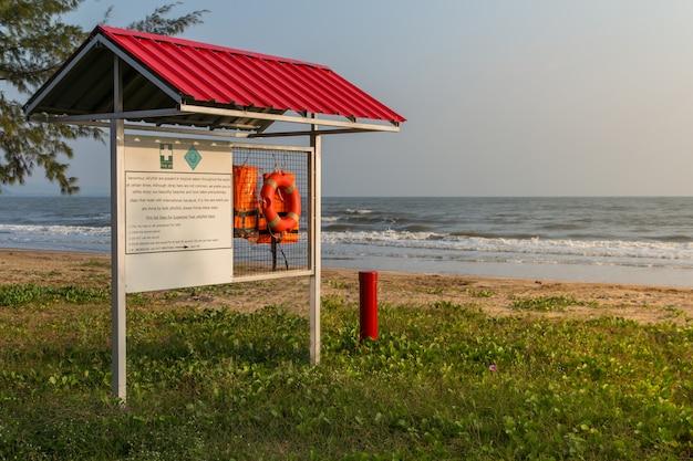 Gilets de sauvetage orange suspendus sur un support avec une étiquette d'avertissement pour les premiers secours sur fond de plage