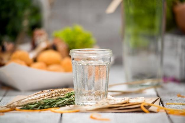 Gin avec une branche de citron et de genévrier sur une vieille table en bois