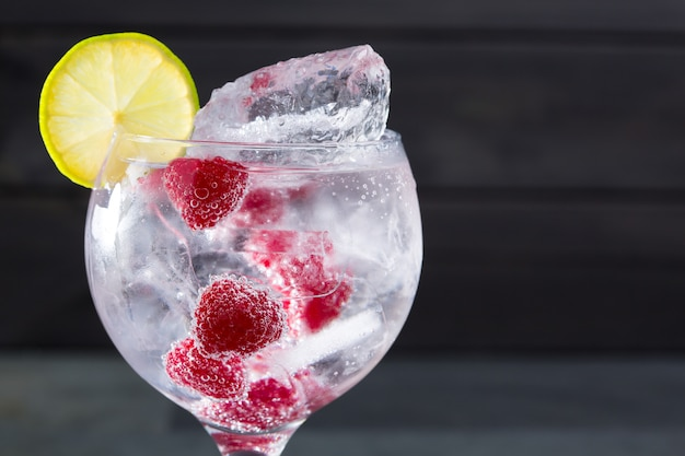 Gin tonic cocktail avec gros plan macro framboise et glace