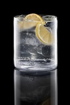 Gin et tonique dans le verre rocks isolé sur fond noir