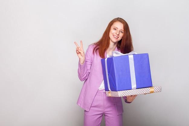 Gingembre belle fille tenant une boîte de cadeaux et avoir un air heureux et montrant un signe av à la caméra. prise de vue en studio