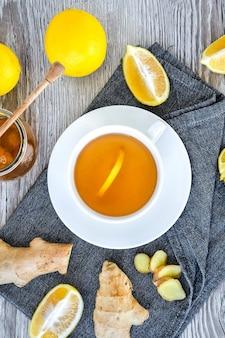 Gingembre chaud stimulant l'immunité boisson naturelle vitaminée avec des agrumes, du miel et des ingrédients dans un style rustique sur fond de bois. thé à la camomille. concept sain