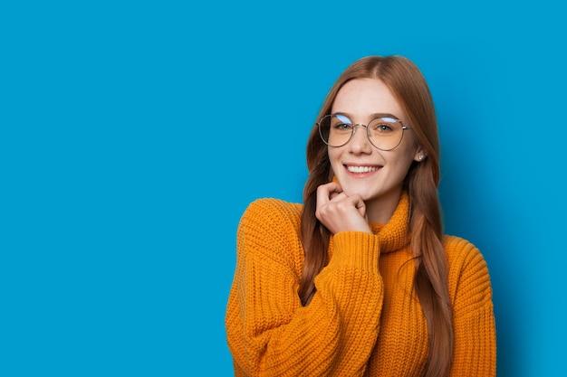 Gingembre jeune femme caaucasienne avec des taches de rousseur et des lunettes touchant son menton et sourire sur un mur de studio bleu avec espace libre