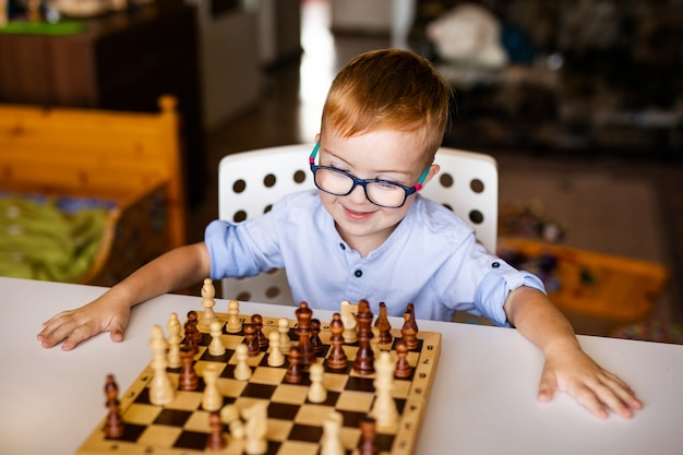 Ginger boy avec le syndrome de down jouant aux échecs à la maison