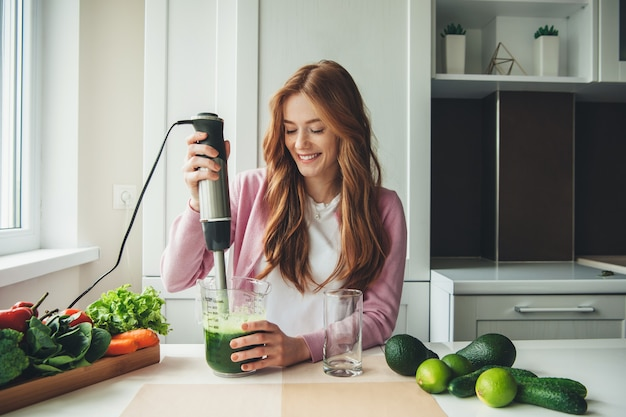 Ginger caucasian lady avec des taches de rousseur faisant du jus de citron vert et d'avocat à l'aide d'un presse-agrumes électrique