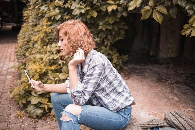Ginger femelle avec téléphone dans la rue avec des buissons