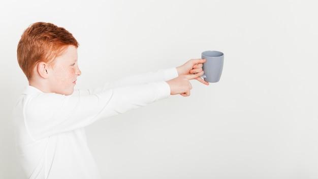 Ginger garçon tenant une tasse