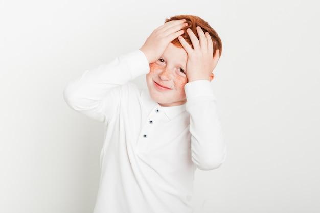 Ginger garçon touchant sa tête