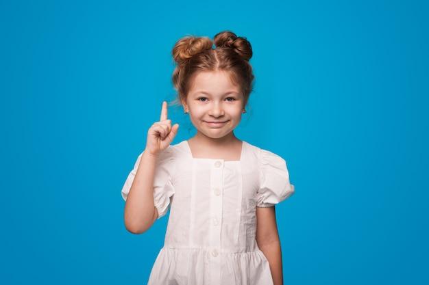 Ginger girl pointant vers le haut avec l'index portant une robe blanche sur un mur bleu