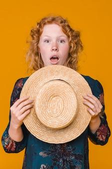 Ginger surpris jeune femme tenant un chapeau de paille