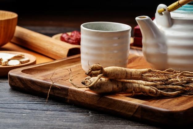 Le ginseng et la tasse de thé sont sur la table