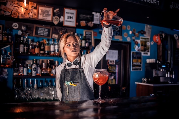 Girl barman crée un cocktail dans le portier
