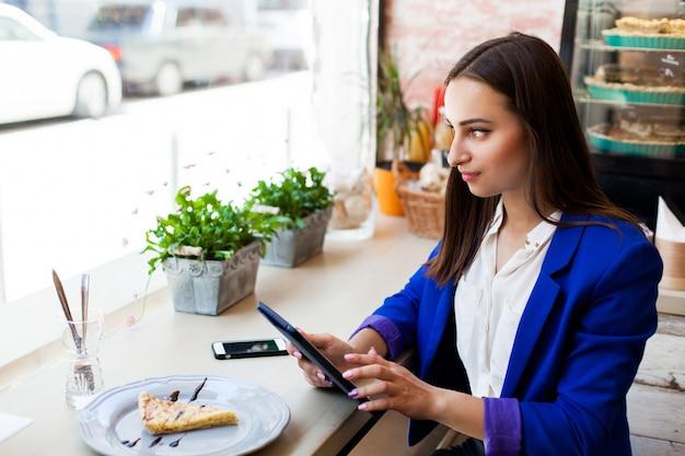 Girl dans un café lit quelque chose sur la tablette