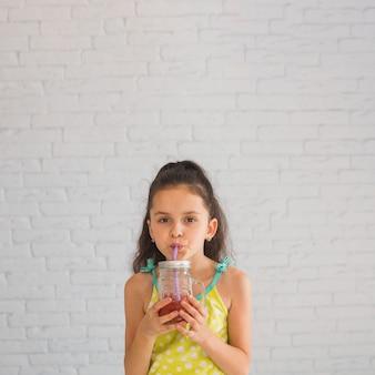 Girl, debout, contre, mur, boire, smoothies fraises