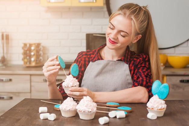 Girl decoration cup cakes avec crème blanche et blue cake-pops à table en bois de cuisine