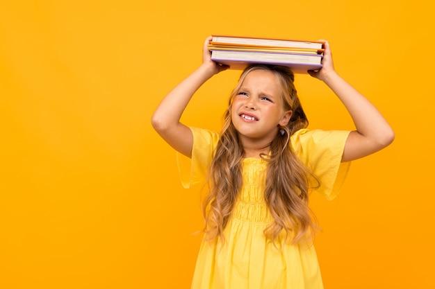 Girl détient une pile de livres sur la tête sur un mur jaune avec copie espace