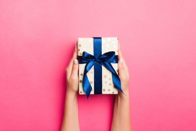 Girl hands holding craft paper gift box avec comme cadeau pour noël ou d'autres vacances sur fond rose