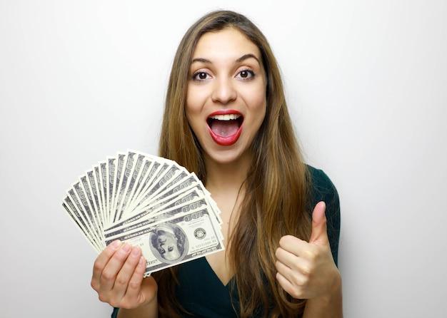 Girl holding billets d'argent, montrant les pouces vers le haut