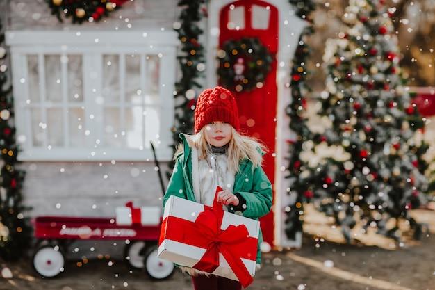 Girl holding cadeau blanc et rouge contre la décoration de noël