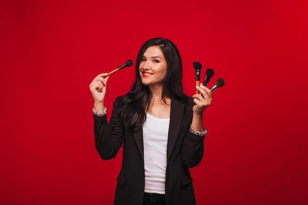 Girl holding pinceaux de maquillage sur fond rouge