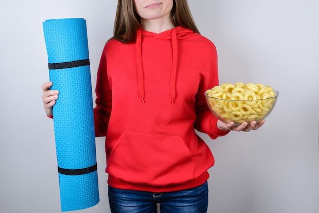 Girl holding plaque avec de la nourriture et tapis de sport bleu isolé fond gris