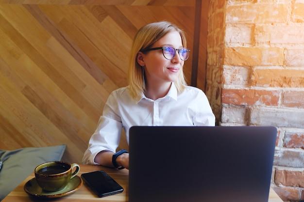 Girl manager, pigiste, femme d'affaires travaillant sur un ordinateur portable.
