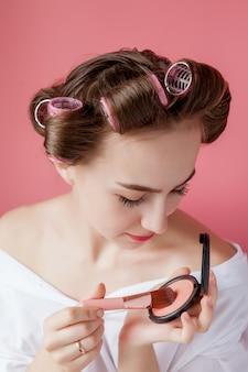 Girl putting eye crayon couleur sur les yeux à la recherche dans un miroir de poche souriant heureux sur rose