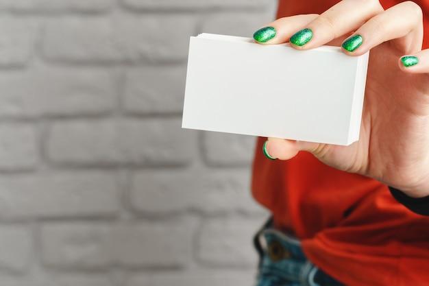 Girl's hand holding carte de visite blanche vierge bouchent