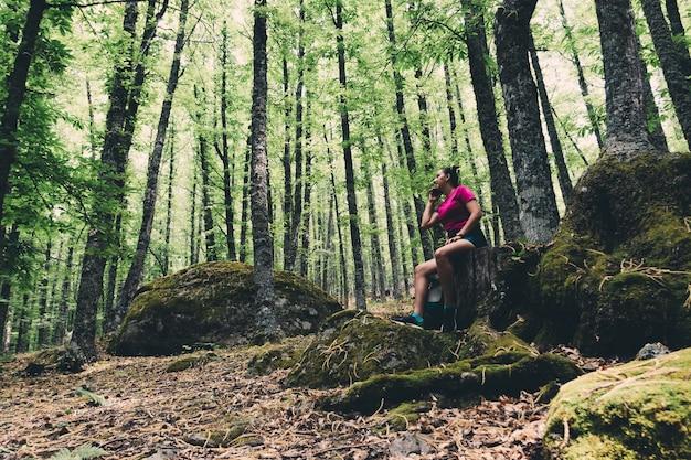 Girl scout parlant au téléphone dans les bois.