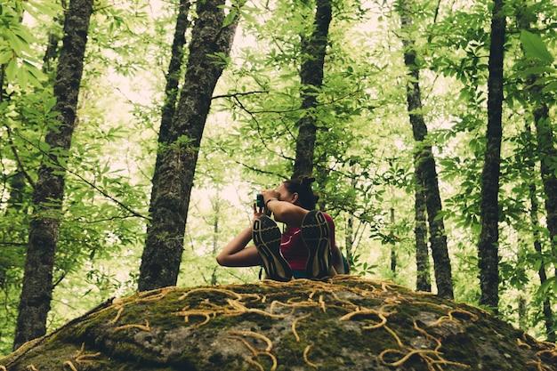 Girl scout avec un sac à dos assis sur un rocher géant et regardant la forêt avec des lunettes.