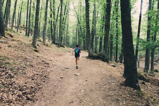 Girl scout avec un sac à dos et un bâton en cours d'exécution et de randonnée dans la forêt.
