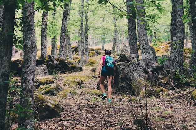 Girl scout avec un sac à dos et un bâton de randonnée dans la forêt.