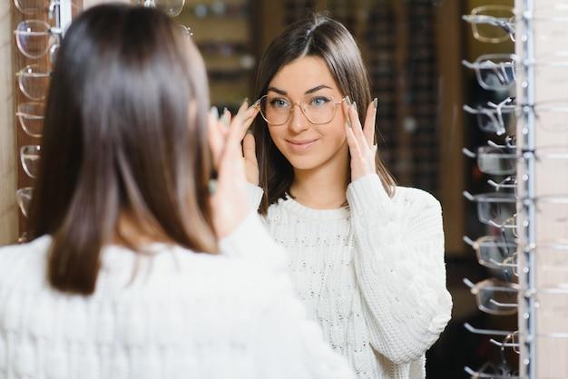 Girl shopping pour les lunettes sur la saison de vente en magasin d'optique.